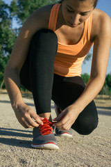 Woman tying laces of running shoes