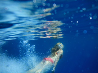 underwater view of young girl diving in crystal clear open waters