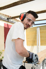 handsome young man carpenter working with electric tool on wood timber in construction site