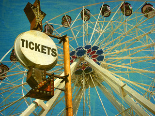 aged and worn vintage photo of ferris wheel and ticket sign