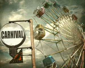 aged and worn vintage photo of carnival sign and ferris wheel