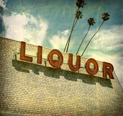 aged and worn vintage liquor store sign with palm trees