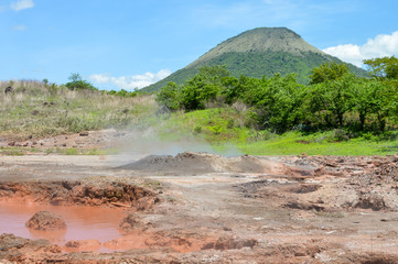 Landscapes of San Jacinto near Telica volcano with the hot bubbling mud pools originating from the volcanic activity on the foreground, near Leon, Nicaragua