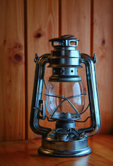 Old kerosene lantern on background wood
