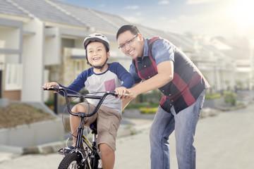 Dad teaching his son to ride a bike