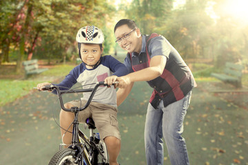 Happy father trains his son to ride a bike