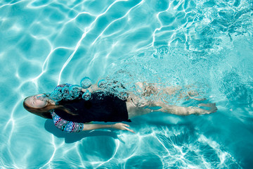 girl swimming underwater on her back