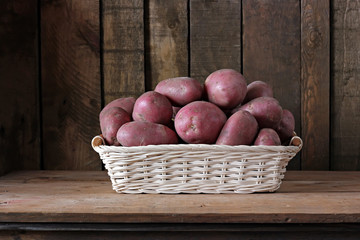 Still life with potatoes in a basket.
