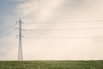 Tall pylons on a green field