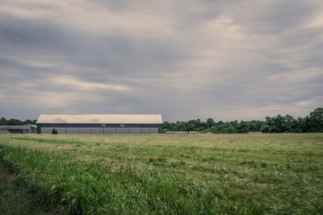 Barn on a field in cloudy weather