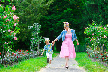 Happy Mother and son walking in summer park with flowers