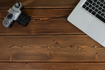 Work space for photographer, designer or hipster style. Have a laptop, film camera on wooden table.