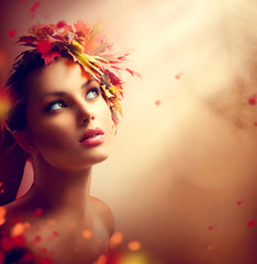Romantic autumn girl with colorful yellow and red leaves on her head