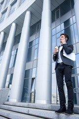 Cheerful young man in suit is working outdoors