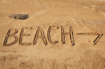 The word Beach with an arrow written in the sand on the beach