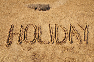 The word Holiday written in the sand on the beach