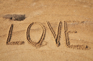 The word Love written in the sand on the beach