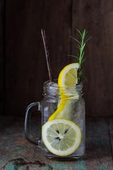 Lemonade with fresh lemon and rosemary in glass