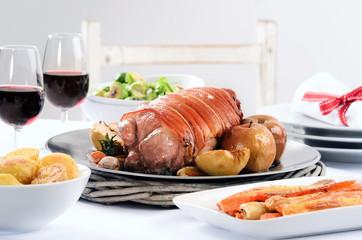 Pork roast dinner with vegetable, potato sides and wine for chri