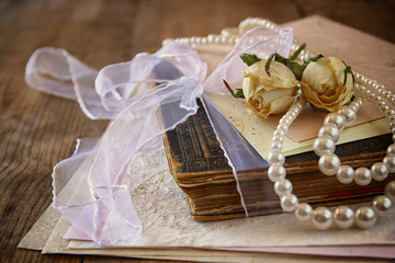 selective focus image of dry roses, white pearls necklace and old vintage books
