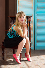 Girl 6 years old in  dress sits on a chair near the wall