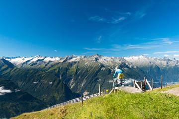 enduro biker riding trail in summer austrian alps on wildkogel with epic view