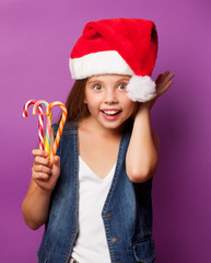 girl in red Santas hat with candy