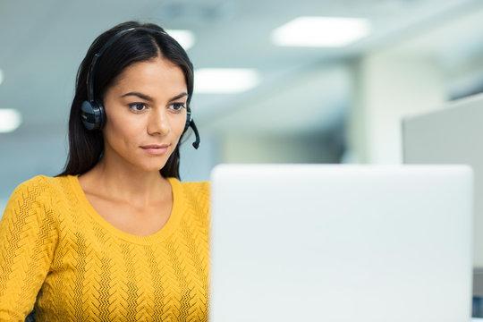 Businesswoman in headphones using laptop