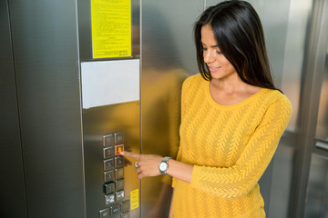 Happy businesswoman pushing elevator button