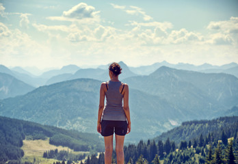 Young woman admiring a mountaintop view Wall mural