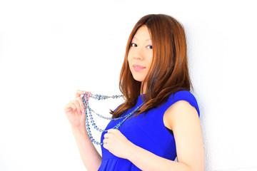 ネックレスを持つ青いワンピースの女性