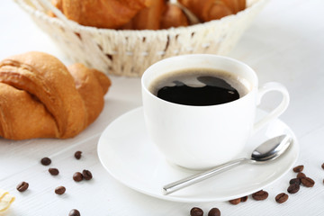 Delicious croissants with cup of coffee on white wooden backgrou