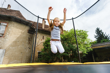 Cute preschooler girl jumping on trampoline
