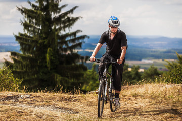 Biking in the Franconian Hills in Northern Bavaria. Young man on