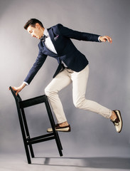 young handsome businessman in studio with chair jumping