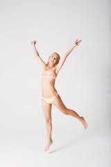 Joyful blond woman in a bathing suit jumping