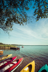 Colorful kayaks moored on lakeshore, Goldopiwo Lake, Mazury, Pol