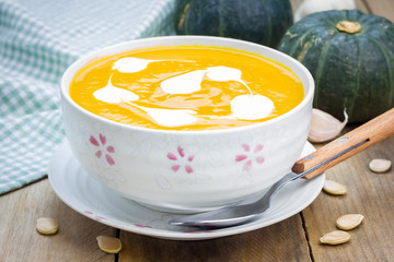 Pumpkin soup with sour cream on a wooden table