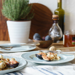 Starter of mozzarella and fresh figs with balsamic and honey dressing and thyme leaves. Selective focus