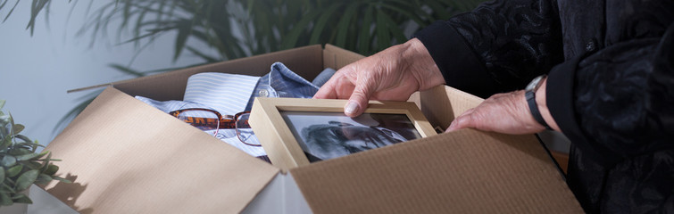 Woman packing dead husband's photography