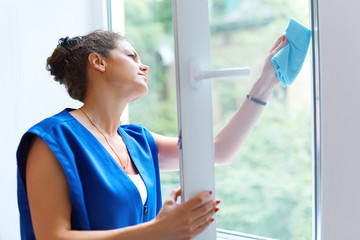 Attractive Woman Washing the Window. Cleaning Company worker wor