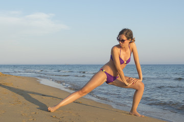 Girl in bikini stretching and exercising at the beach