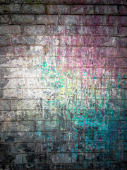Dirty brick wall painted with spots of paint colors