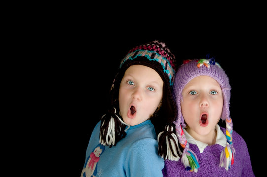 two girls in winter caps singing with black background