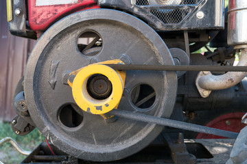 Engine of used mini tractor: black pulley and belt.