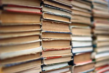 Stacks of old hardback and paperback books. Background image