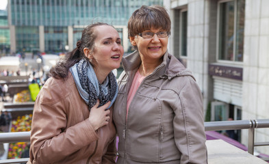Outdoor family portrait of pension age Mother and her daughter in the city, smiling and looking around. Two generation, happiness and care  concept