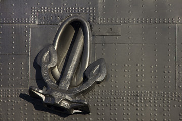 Closeup view of an anchor of ship on deck armour background
