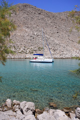 calm bay with catamaran framed by mountains