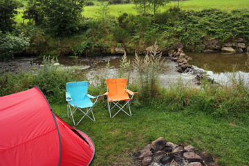 Campsite with a canvas tent and camp furniture near a creek